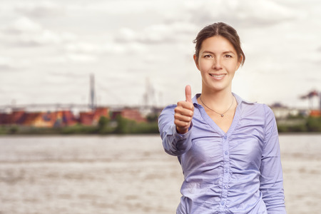 succesful: Happy smiling attractive woman giving a thumbs up gesture of success and approval, upper body portrait in front of an urban river or waterway with copyspace
