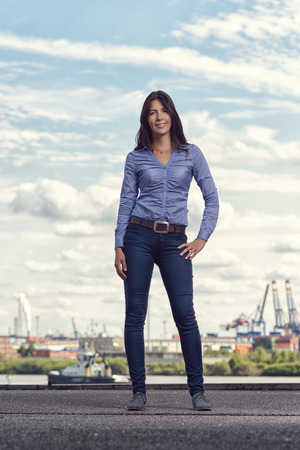 women jeans: Attractive trendy woman wearing close fitting jeans posing outdoors on a promenade with her hand on her hip smiling at the camera Stock Photo