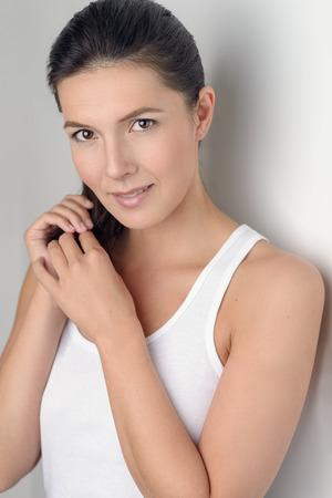 elasticidad: Mujer bonita joven en Casual camisa sin mangas blanca celebraci�n de su pelo y sonriendo a la c�mara mientras se inclina la espalda contra la pared.
