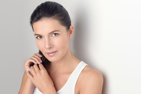 Mooie jonge vrouw in casual wit mouwloos shirt die haar haar en lacht naar de camera terwijl leunt met haar rug tegen de muur.