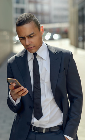 phone message: Half Body Shot of a Young Businessman Messaging Someone on his Mobile Phone While Walking in the Street