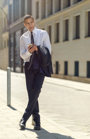 man in suit: Businessman sitting on a metal bollard or pole on an urban sidewalk reading an sms or text message on his mobile phone with a serious expression and his jacket over his arm