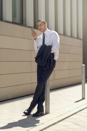 male body: Businessman sitting on a metal bollard or pole on an urban sidewalk reading an sms or text message on his mobile phone with a serious expression and his jacket over his arm