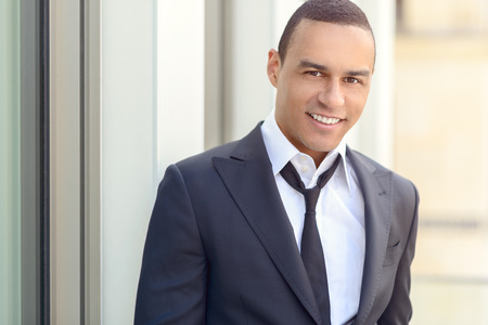head collar: Attractive smiling businessman with a loosened tie and his collar unbuttoned looking at the camera, closeup head and shoulders Stock Photo