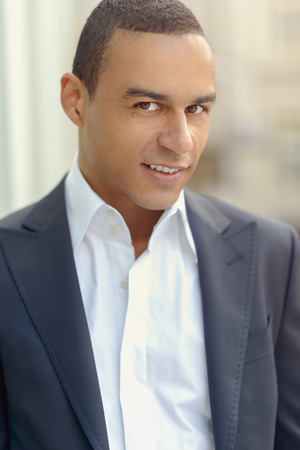 head collar: Attractive smiling businessman with his collar unbuttoned looking at the camera, closeup head and shoulders Stock Photo