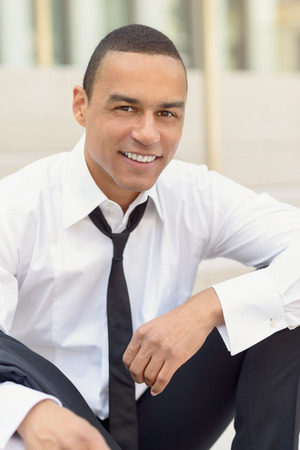 unbuttoned: Attractive smiling businessman with a loosened tie and his collar unbuttoned looking at the camera, closeup head and shoulders Stock Photo