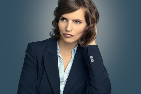 business skeptical: Attractive pensive woman sitting with her chin resting on her hand staring into space with a serious expression, over grey Stock Photo