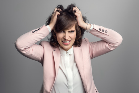 venting: Attractive stylish young woman in a pink jacket tearing at her brown hair with her hands as she vents her frustration, over grey
