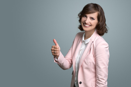 successful woman: Smiling enthusiastic young woman giving a thumbs up sign of approval, agreement and success, isolated on grey