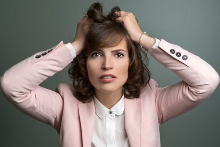 tearing: Attractive stylish young woman in a pink jacket tearing at her brown hair with her hands as she vents her frustration, over grey