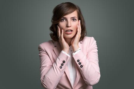 Mujer joven reaccionar en estado de shock y el horror con la boca abierta y las manos levantadas a sus mejillas mientras mira de reojo a la izquierda del marco, sobre gris Foto de archivo - 44085472