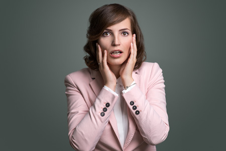 mistake: Young woman reacting in shock and horror with her mouth agape and hands raised to her cheeks as she looks sideways to the left of the frame, over grey Stock Photo