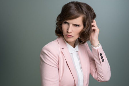befuddled: Attractive young brunette businesswoman in a stylish pink jacket scratching her head with a puzzled perplexed frown, over grey