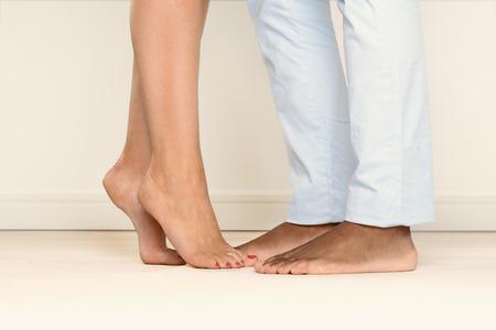 맨발 인간의 발과 로맨틱 한 연락의 또 다른 암시를 마주 발끝으로 서있는 여자의보기를 닫습니다