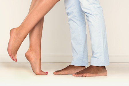 barefoot women: Close up view of the feet of a barefoot man and a woman standing on tiptoe facing one another suggestive of a romantic liaison