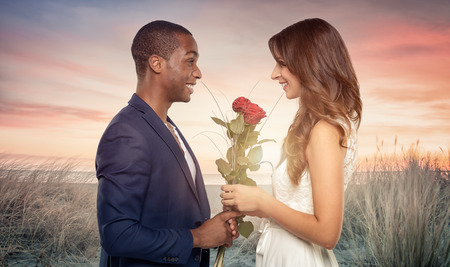 clutches: Smiling romantic handsome young African man proposing to his sweetheart as he clutches a bunch of long stemmed red roses in his hand, sideview in the sunset on a beach Stock Photo