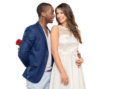 multi racial: Romantic young man embracing his girlfriend with a loving smile as he hides a surprise red rose behind his back, Valentines Day, anniversary or engagement concept, multi racial couple, isolated on white