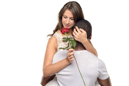 suitor: Sentimental young woman hugging her boyfriend or sweetheart as she smiles tenderly down at a single red rose he has just given her, symbolic of love and romance or Valentines Day, multiracial couple