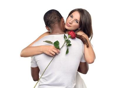 tenderly: Sentimental giovane donna abbraccia il suo fidanzato o fidanzata come sorride teneramente gi� in una sola rosa rossa che ha appena dato il suo, simbolo di amore e di romanticismo o San Valentino, coppia multirazziale