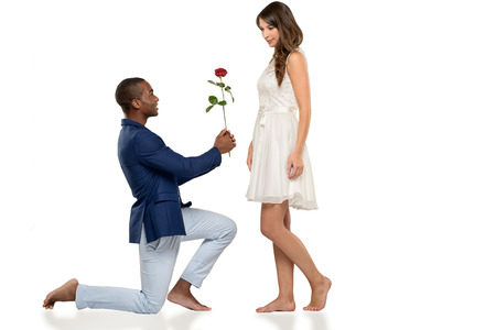 kneeling man: Romantic hipster barefoot young man kneeling on the floor proposing to his sweetheart declaring his undying love in a tender scene, multiracial couple Stock Photo