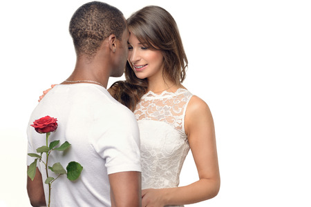 tenderly: Romantic young man with a pretty woman hiding a red rose behind his back as he prepares to surprise her on Valentines Day or with a wedding proposal, multiracial couple with the woman smiling tenderly