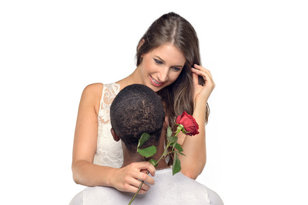 courtship: Sentimental young woman hugging her boyfriend or sweetheart as she smiles tenderly down at a single red rose he has just given her, symbolic of love and romance or Valentines Day, multiracial couple