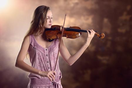 Mooie jonge vrouwelijke violist in een stijlvolle roze outfit staande spelen van de viool als ze geeft een klassiek recital in de academie of praktijken voor een optreden