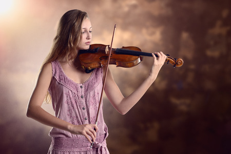 woman violin: Pretty young female violinist in a stylish pink outfit standing playing the violin as she gives a classical recital at the academy or practices for a performance Stock Photo