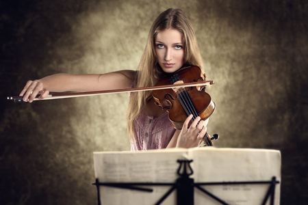 recital: Pretty young female violinist in a stylish pink outfit standing playing the violin as she gives a classical recital at the academy or practices for a performance Stock Photo