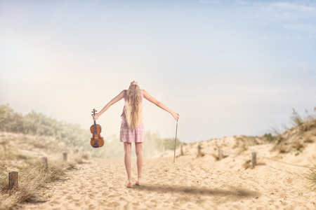 Rear View of a Young Female Musician with Violin Instrument Spreading her Arms While Tilting her Head Back on a Very Sunny Day.