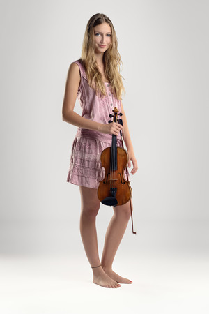 Pretty barefoot young woman standing in a summer dress with a violin and bow in her hand smiling at the camera, studio background Stock Photo