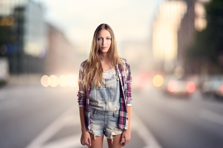 jumpsuit: Three Quarter Shot of a Young Blond Woman Wearing Trendy Short Jumpsuit Denim with Checkered Long Sleeved Shirt standing on a street in the evening with headlights in the background