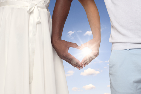shaped hands: Young Couple Crossing Their Arms and Forming a Heart Shaped Hands Together Against sunny blue sky