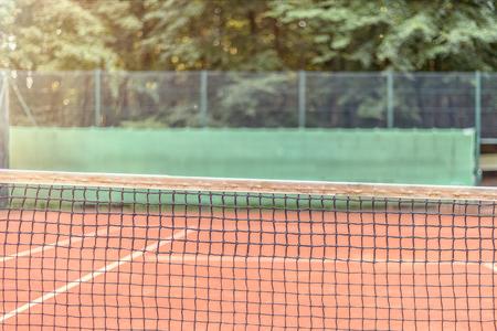 Uitzicht over de lengte van het net op een all-weather tennisbaan richting kant hekwerk met advertenties, hof is leeg conceptuele van sport, kampioenschappen en toernooien