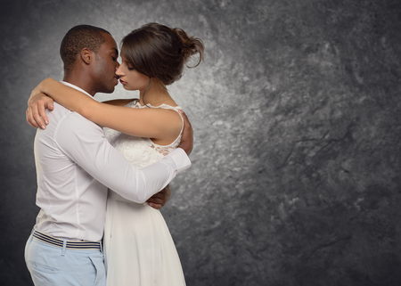 sweethearts: Young couple deeply in love hugging and kissing passionately in a tender moment, side view upper body of a multiracial couple