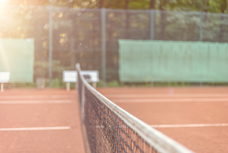 tennis clay: View across the length of the net on an all-weather tennis court towards side fencing with adverts, court is empty conceptual of sport, championships and tournaments