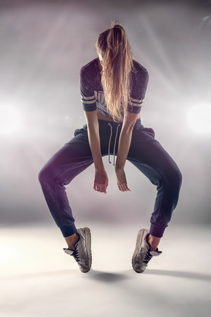 dancers: Female Hip Hop Dancer in Tip Toe Position with her Hair Covering her Face Against Brown Wall Background In the Studio.