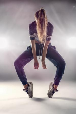 baile hip hop: Mujer bailar�n de Hip Hop en la Posici�n Tip Toe con su pelo que cubre la cara contra el fondo de Brown pared en el estudio.