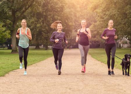 Vier gesunde junge Frauen Joggen im Park am Nachmittag mit einem Hund.