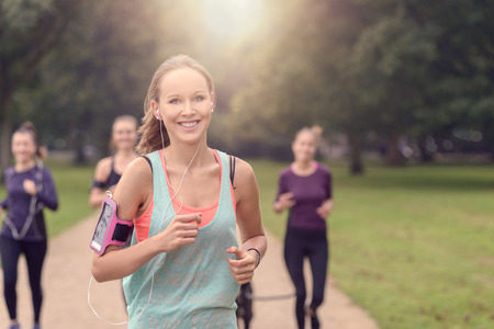 Half Body Shot of an Athletic Pretty Young Woman Smiling at the Camera While Jogging at the Park with Other Girls, with copy space on the right Stock Photo