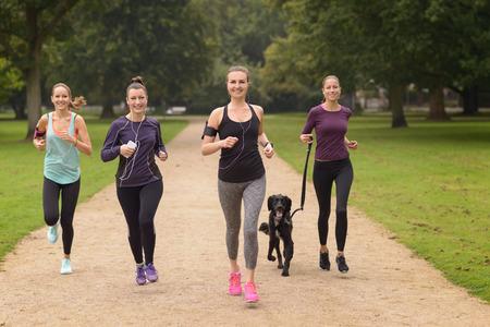 dog running: Cuatro saludables Mujeres jóvenes a correr por el Parque de la tarde con un perro de mascota.