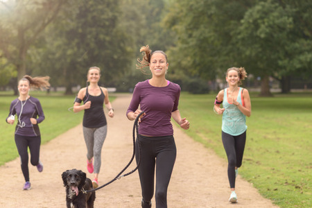 smartphone: Half Body Shot of an Athletic Pretty Young Woman Smiling at the Camera While Jogging at the Park with Other Girls, with copy space on the right Stock Photo