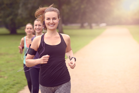 Half Body Shot of an Athletic Pretty Young Woman Smiling at the Camera While Jogging at the Park with Other Girls, with copy space on the right Zdjęcie Seryjne