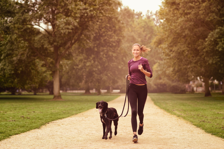 Full length Shot of a Healthy Young Woman Jogging in the Park with her Black Pet Dog
