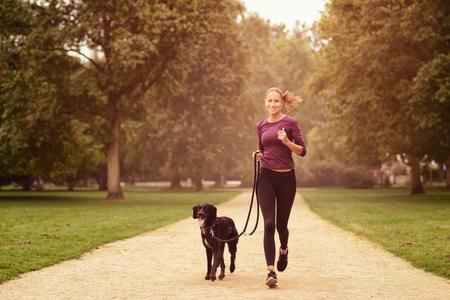 Volledige lengte shot van een gezonde jonge vrouw joggen in het park met haar Black Dog Pet Stockfoto