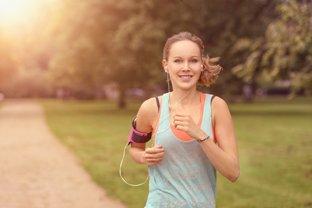 Half Body Shot of a Pretty Athletic Woman Jogging at the Park with Headphones and Smiling at the Camera, with copy space
