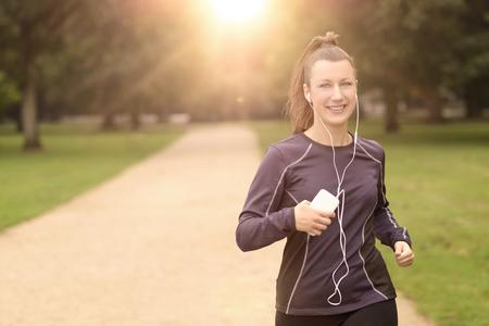 la escucha activa: La mitad Shot cuerpo de un Bastante Mujer Atlética El activar en el parque con los auriculares y sonriendo a la cámara, con copia espacio
