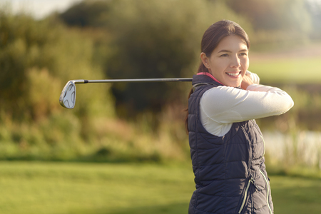 follow through: Smiling friendly young woman golfer looking at the camera after following through with her club after the shot, close up view of her face Stock Photo