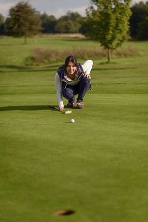 lining up: Female golfer lining up a putt kneeling on the green looking at the hole to check the grass and any camber from a slope Stock Photo