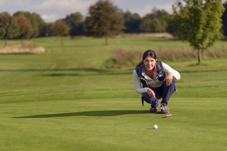 green line: Female golfer lining up a putt kneeling on the green looking at the hole to check the grass and any camber from a slope Stock Photo